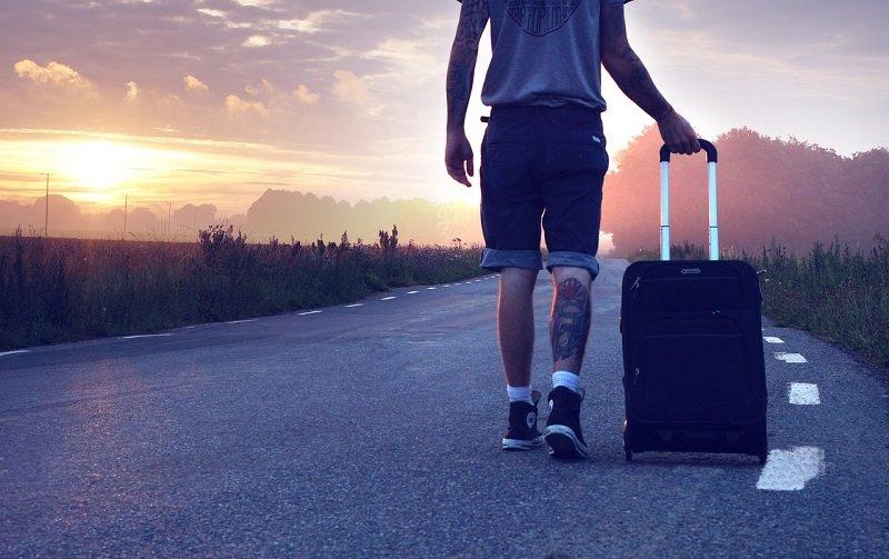 Mężczyzna podróżujący pieszo z walizką