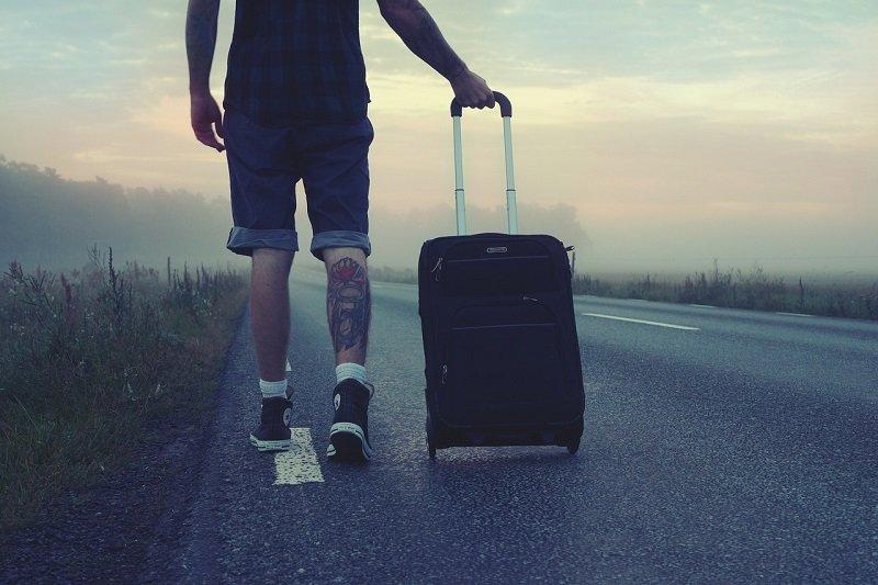 Mężczyzna podróżujący z walizką na kółkach