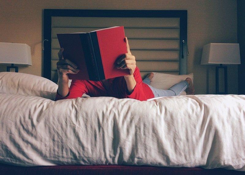 Osoba czytająca książkę na hostelowym łóżku